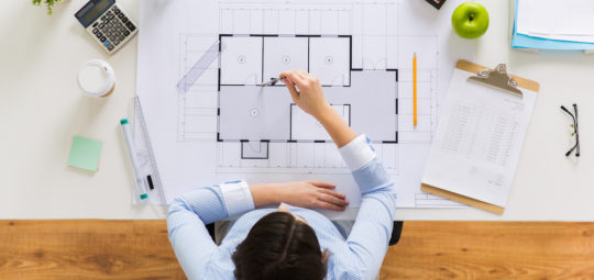 business, architecture, building and construction concept - architect woman with compass measuring blueprint of living house at office